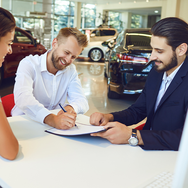 Smiling man and woman buys a car in a car showroom.