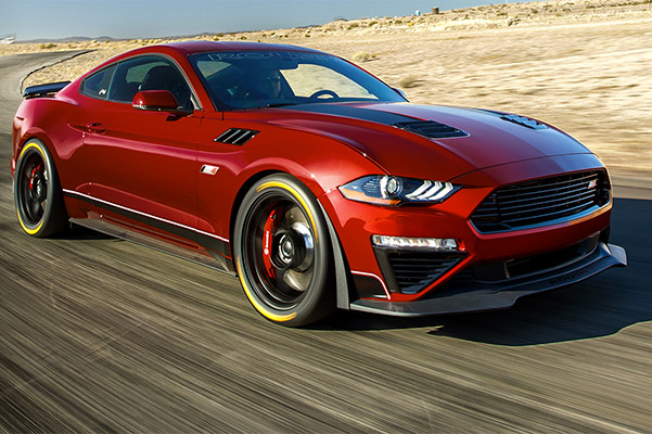 red Ford mustang Roush Performance Vehicle going at high speed on a terrain race track
